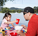 Father and daughter (6-7) having barbecue in park, San Rafael, California, USA